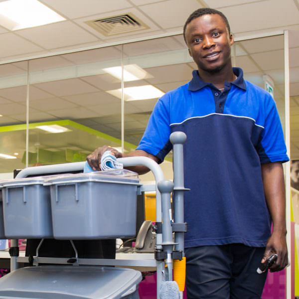 Young Man Cleaner with janitorial trolley