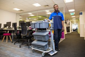 Man with cleaning trolley in an office