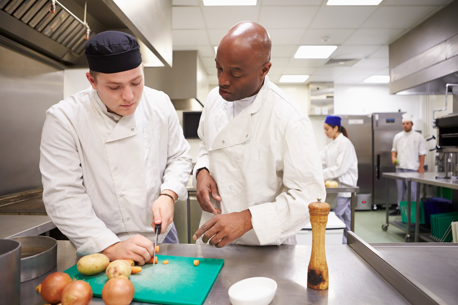 Teacher Helping Students Training To Work In Catering